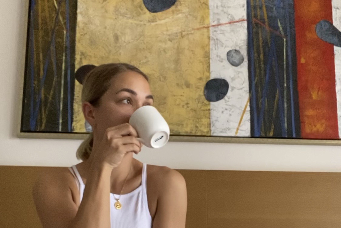 Upper-body shot of person sitting on a wooden bench drinking out of a white mug. White wall in background with large painting hanging.