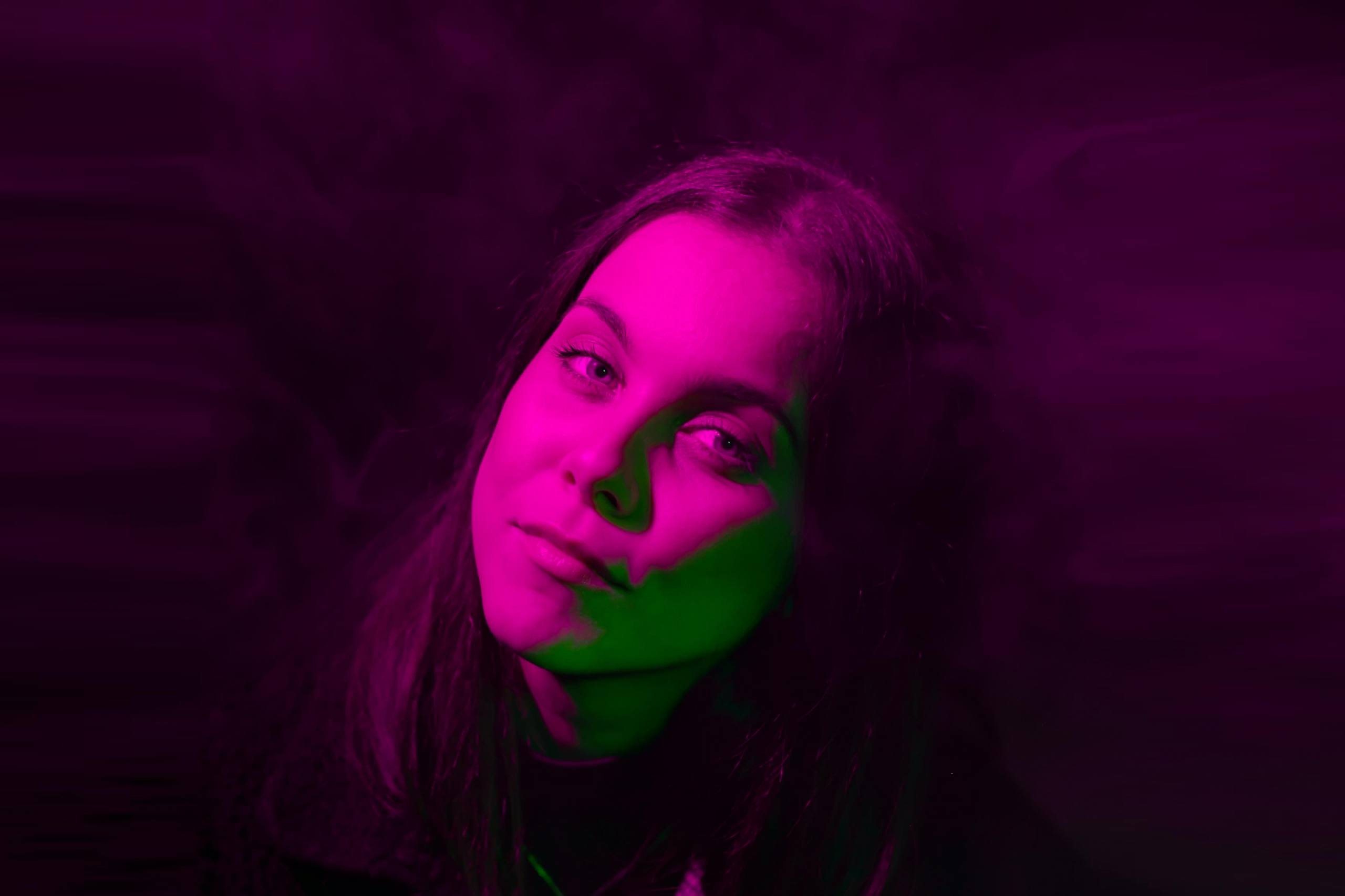 Headshot of an artist with their head slightly tilted looking at camera. Dark purple cloudy background with pink and green lights shining on the artist's face.