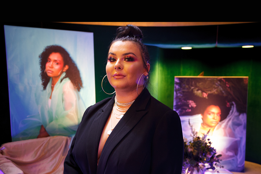 Upper-body shot of an artist wearing hoop earrings and hair in a bun. Standing in a green and black room with two paintings of another person and a couch covered with a pink sheet to the left.