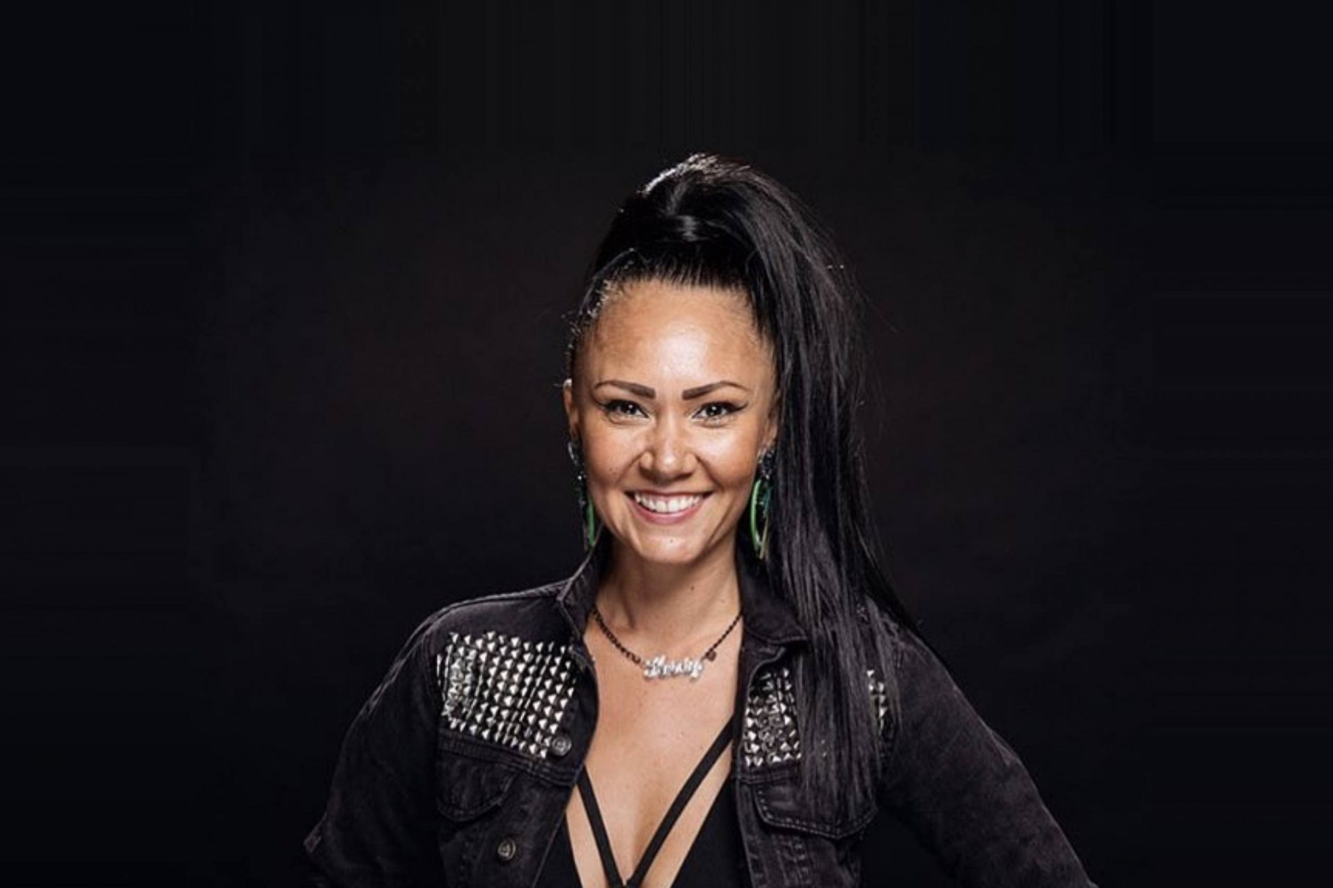 Headshot of a woman with long black hair in pony tail smiling. Black background.