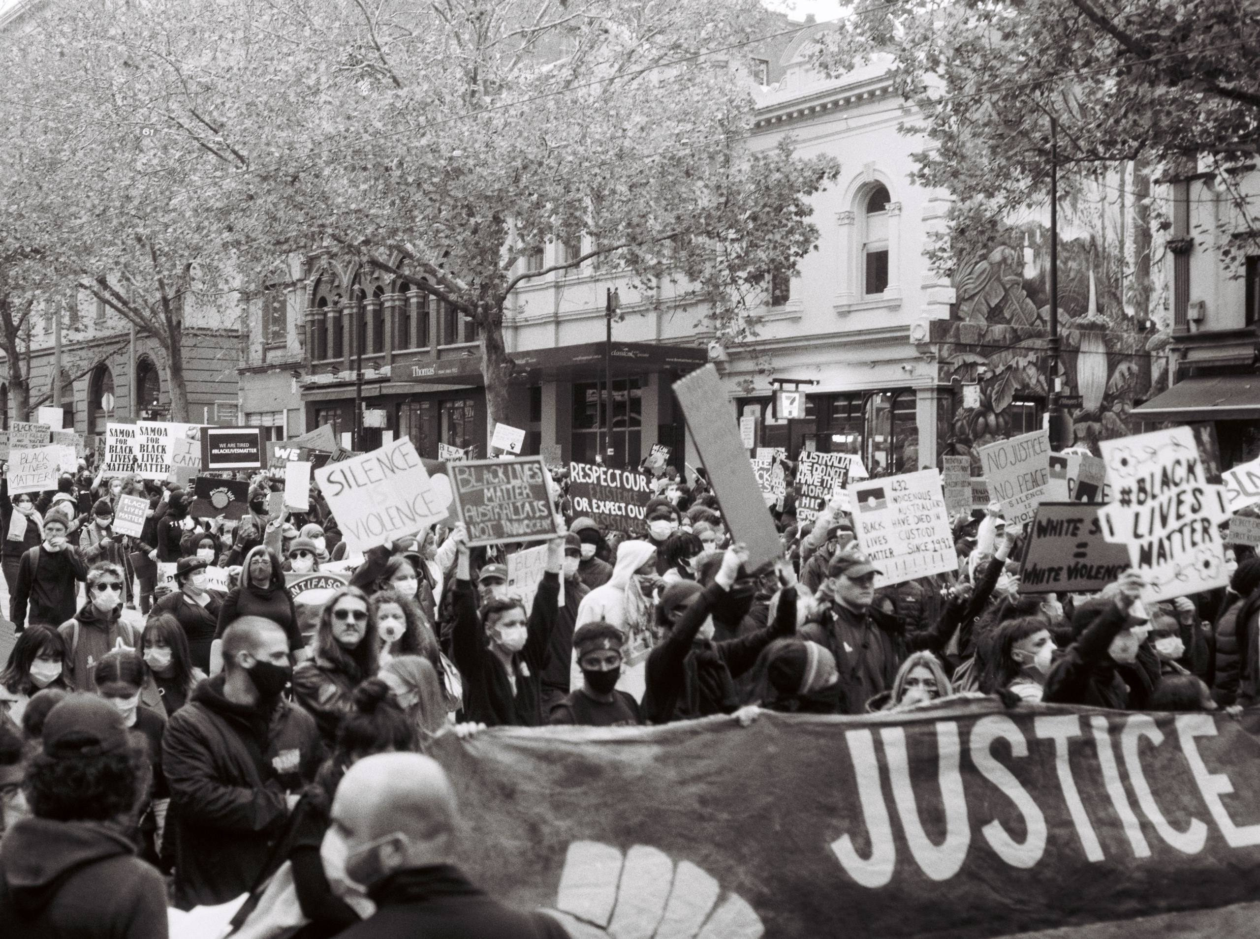 Black and white image of Black lives matter protest in Melbourne with big group of people holding signs. Buildings and trees in background.