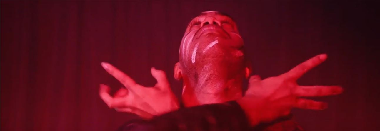 Headshot of a performer with head tilted backwards with hands crossed over below chin and little bit of white paint on face. Red curtains in background and red light shining on performer.