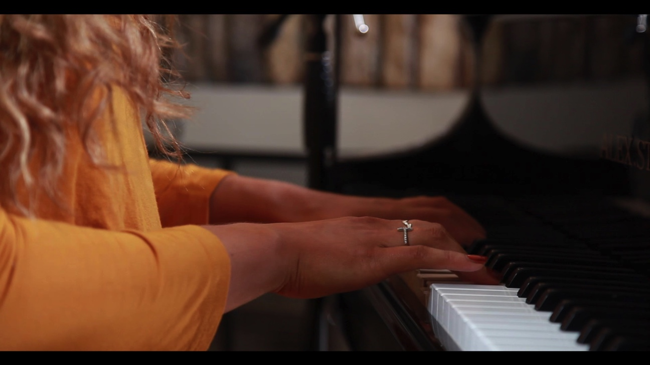 Picture of an artist's arms and hands playing on piano with yellow long sleeve top and blonde curly hair.